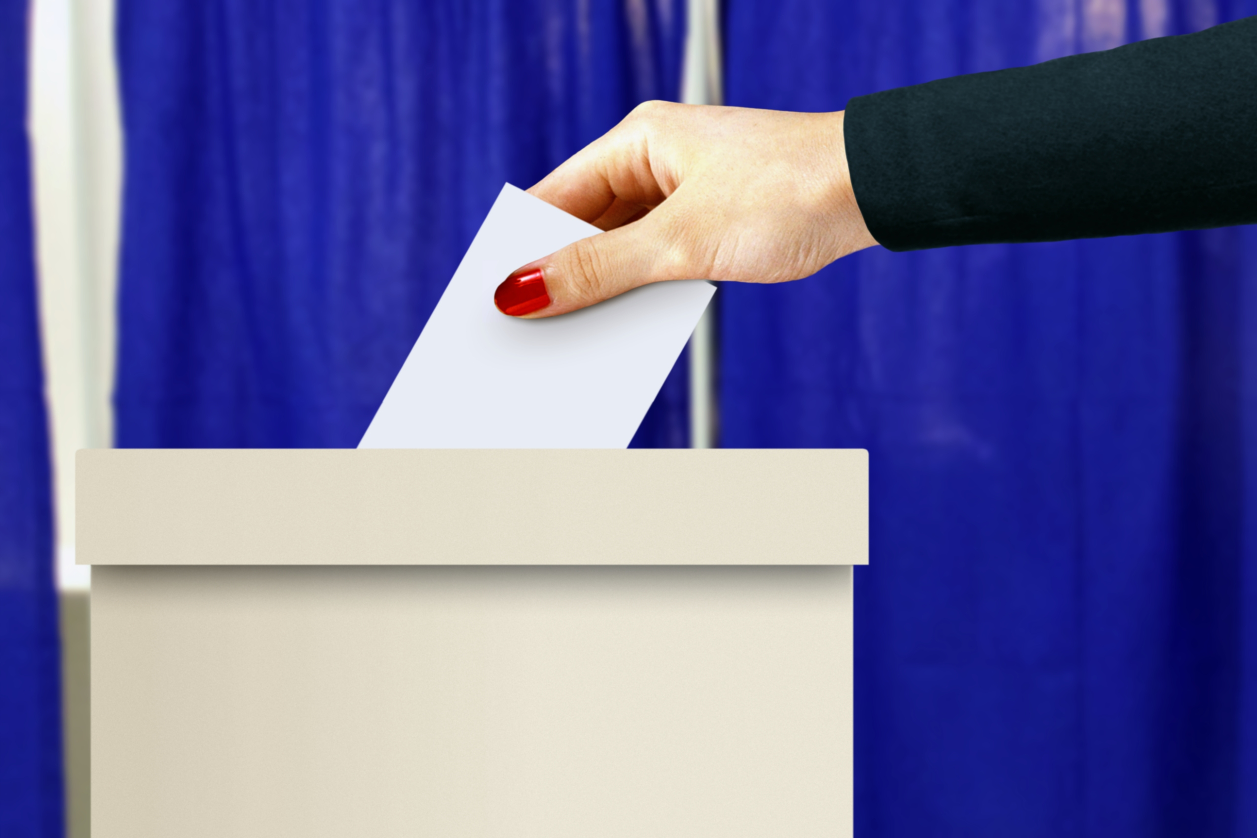 Ballot box with women hand casting a vote