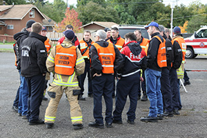 emergency responders form a circle to meet outdoors at the scene of an incident