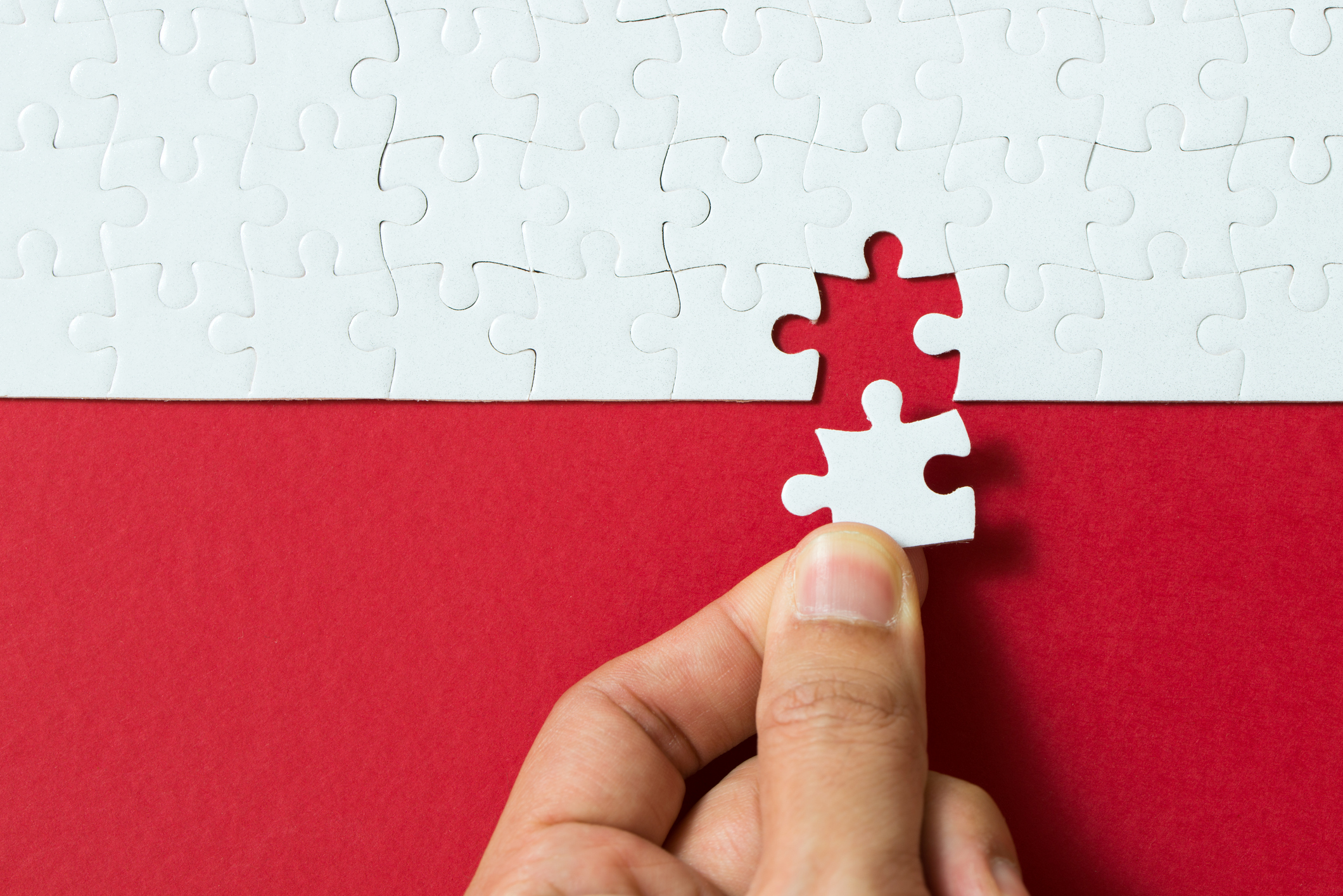 White puzzle pieces on a red background.