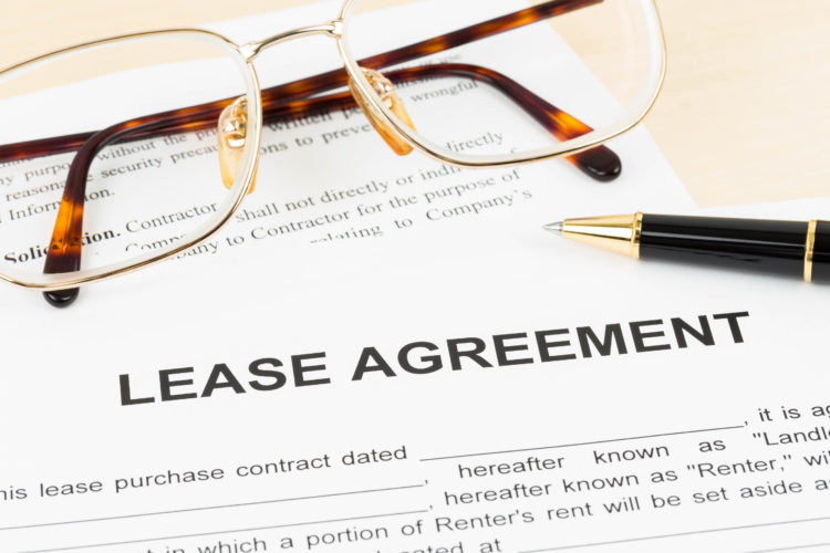 A lease agreement shown with a pair of eyeglasses and a pen