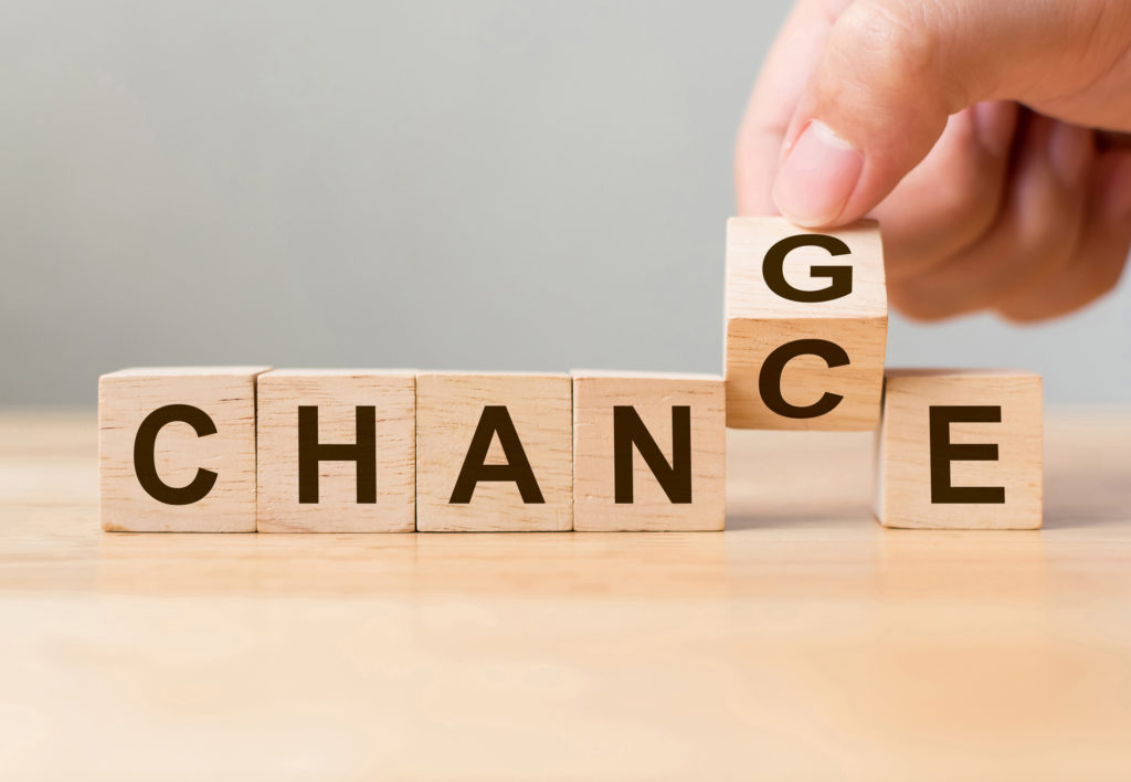 """Hand flip wooden cube with word """"change"""" to """"chance"""""""