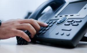 close up employee man hand point to press button number on office telephone
