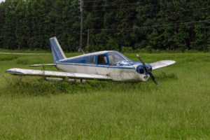 Abandoned blue and white single prop plane in green grass field