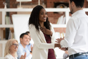 Happy female employee gets rewarded for professional achievement, shaking hands with boss,