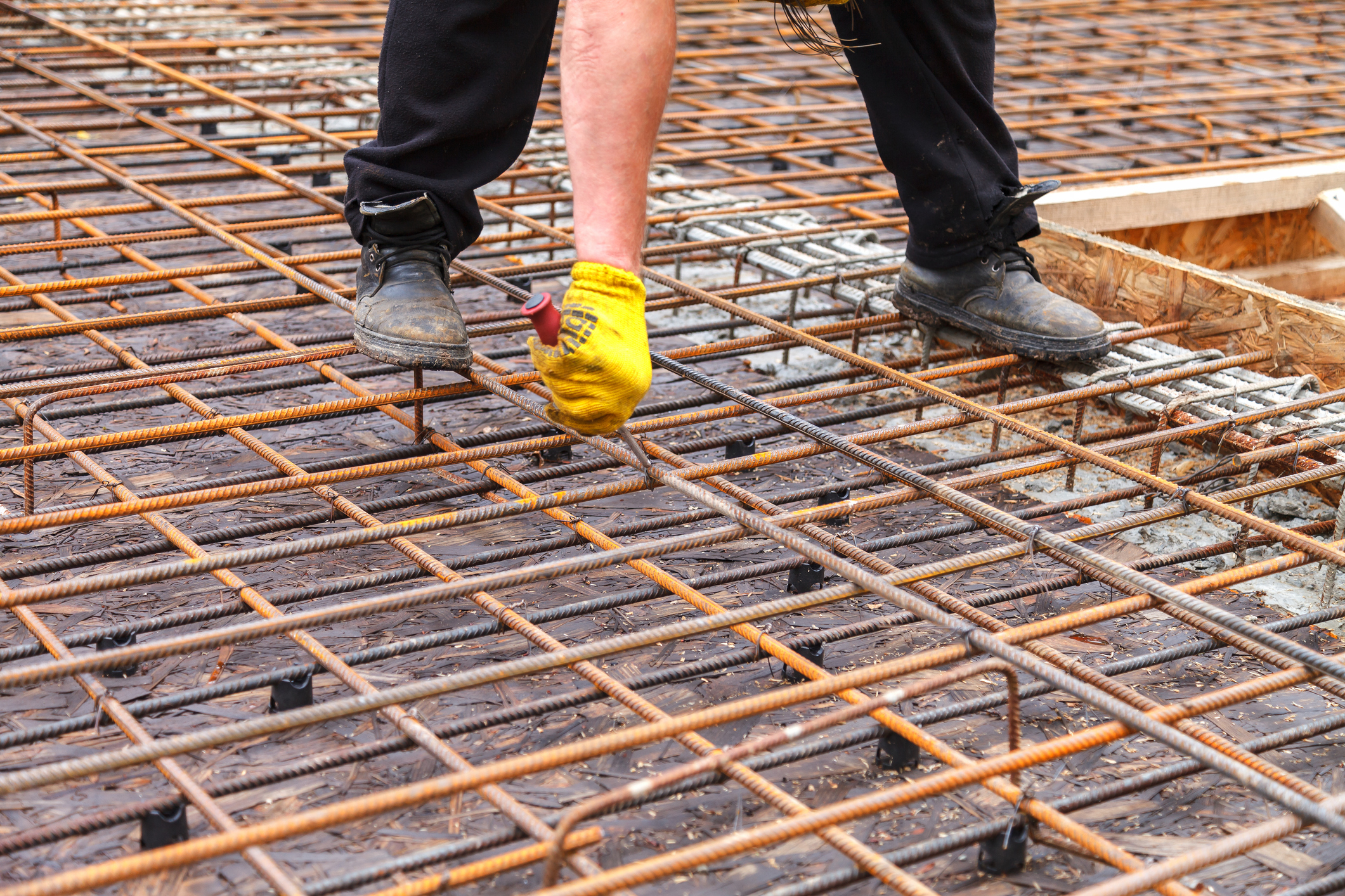 Construction worker ties steel reinforcing bars with wire to strengthen the foundation.