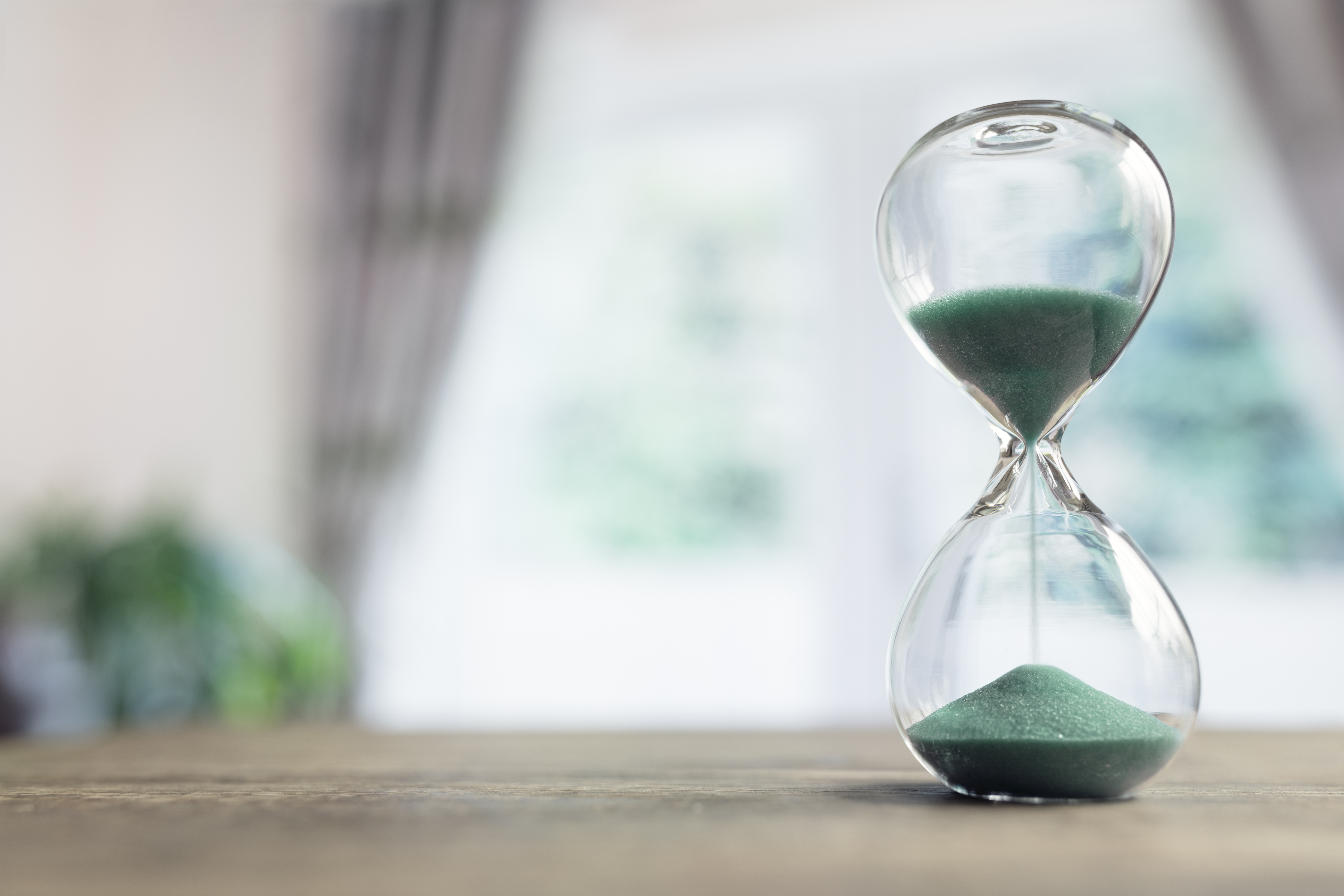 Hourglass time passing on table in room by window