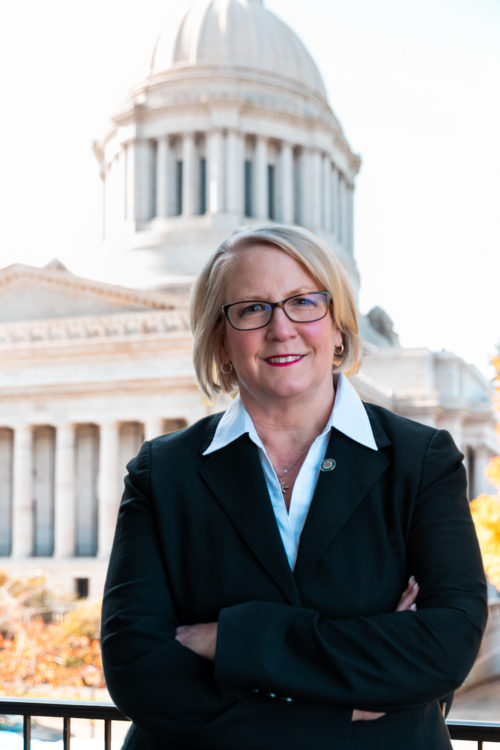 Washington State Auditor Pat McCarthy stands with the state Capitol building in the background.