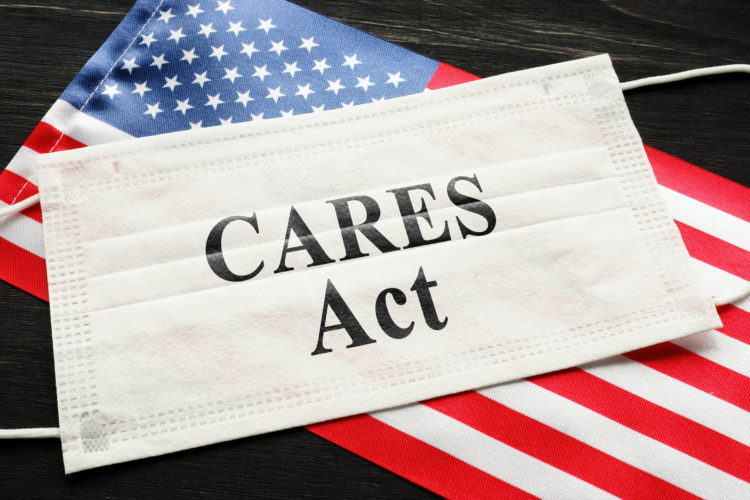 "American flag and mask with sign showing the phrase ""CARES Act."""